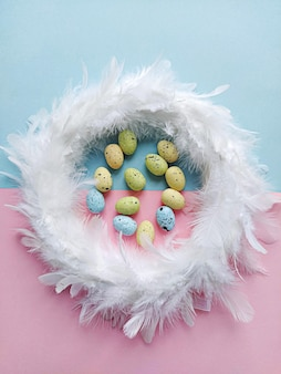 White feathers wreath on lilac floral background with decoration eggs, top view. easter decoration concept