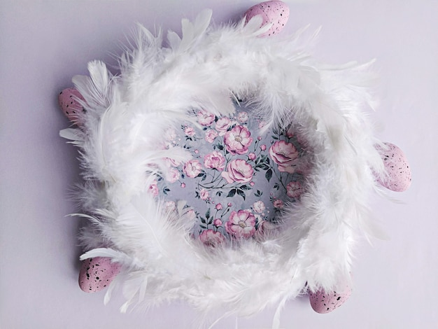 White feathers wreath on lilac floral background with decorative easter eggs, top view. diy easter decoration at home concept