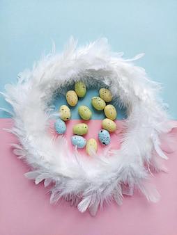 Венок из белых перьев на сиреневом цветочном фоне с декоративными яйцами, вид сверху. концепция пасхального украшения