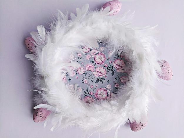 Венок из белых перьев на сиреневом цветочном фоне с декоративными пасхальными яйцами, вид сверху. diy пасхальное украшение дома концепция