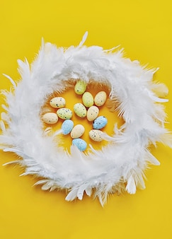 Венок из белых перьев на желтом фоне с мини-искусственными яйцами, вид сверху. концепция пасхального украшения