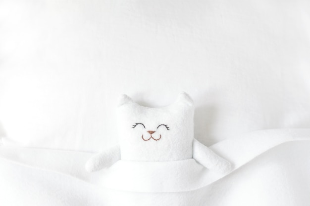 White felt cat sleeping on the bed under a white blanket.