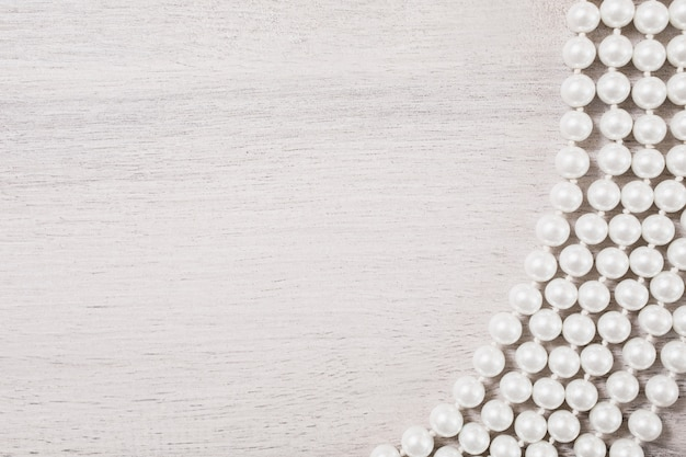 White female beads on white wooden background, female jewelery on a white wooden table