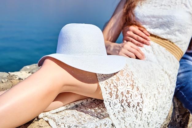 Белая женская шляпа, лежащая на коленях молодой девушки