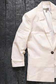 Белая женская куртка на темном деревянном столе. современная модная женская одежда. плоская планировка. вид сверху.