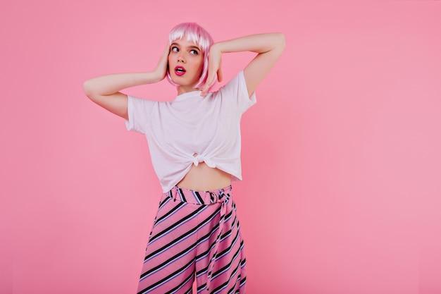 매력적인 peruke에서 감정적으로 포즈를 취하는 캐주얼 티셔츠에 백인 여성 모델. 멀리보고 그녀의 머리를 만지고 분홍색 periwig에서 꿈꾸는 백인 여자의 초상화
