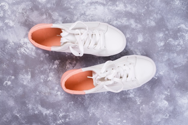 White female sneakers on stone background. flat lay, top view minimal background.