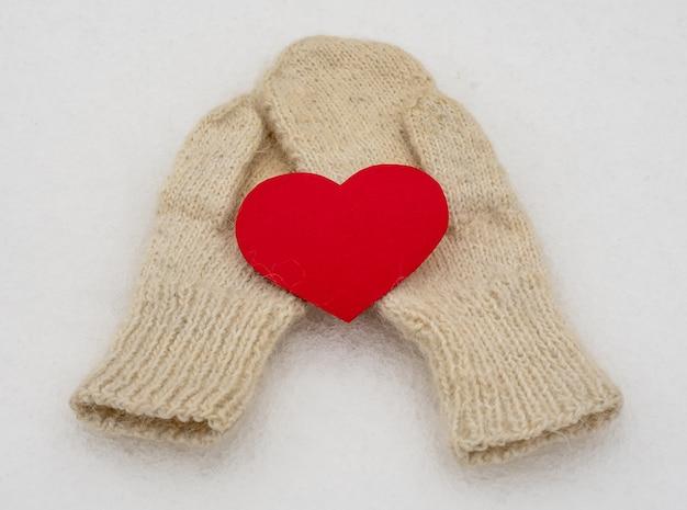 Белые женские шерстяные рукавицы на белом снегу. зимняя одежда. одно красное сердце. день святого валентина.