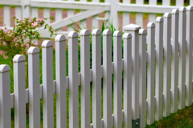 녹색 잔디와 꽃 근접 촬영에 흰색 울타리.
