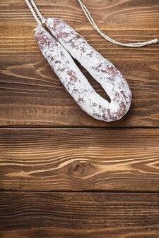 Белая ферментированная колбаса fuet на деревянном столе с пространством для текста.