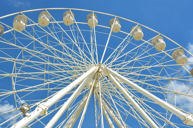 White ferries wheel of the amusement park in the blue sky