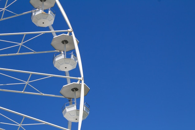 Белое колесо обозрения на голубом небе