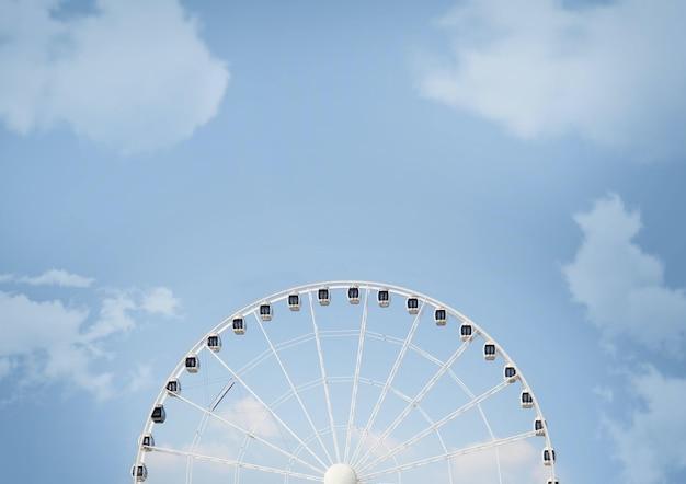 낮에는 햇빛과 푸른 흐린 하늘 아래 흰색 관람차