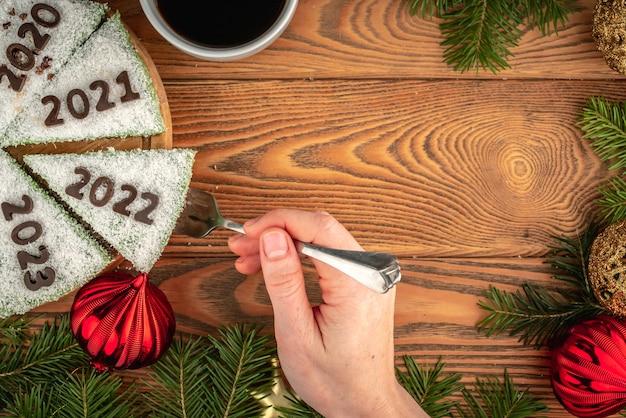 연도를 나타내는 숫자로 장식된 흰색 축제 케이크. 손이 2022라는 숫자가 있는 조각을 꺼내고 있습니다. 새해의 개념입니다. 공간을 복사합니다.