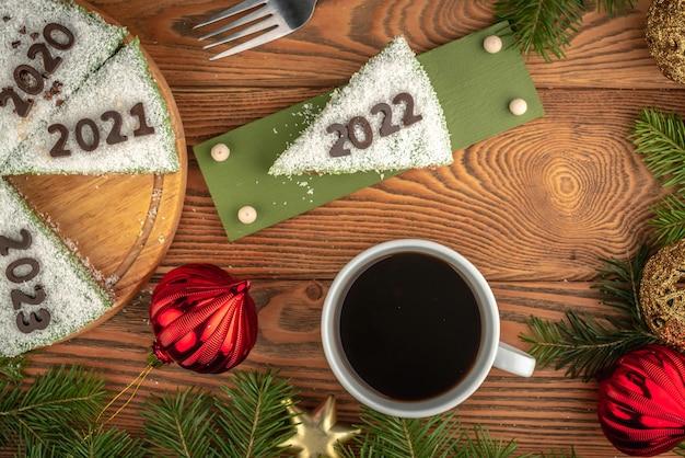 연도를 나타내는 숫자로 장식된 흰색 축제 케이크. 접시에는 2022라는 숫자가 있는 조각이 있습니다. 새해 개념입니다. 평면도.