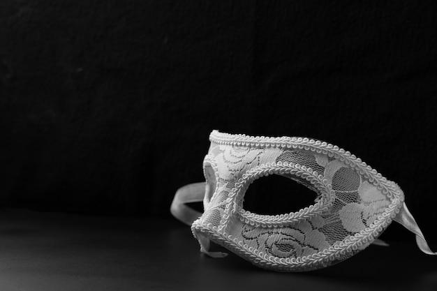 Белая праздничная карнавальная маска стоит на черном столе