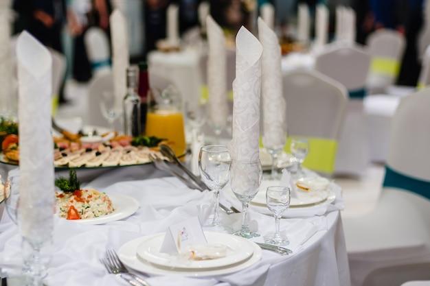 Белый праздничный сервированный стол в ресторане с бокалами и тарелками, приготовленными на ужин