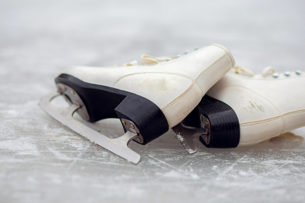 White figure skates lie on an open ice rink