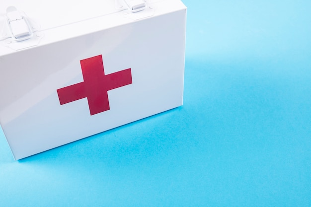 White first aid kit on blue background