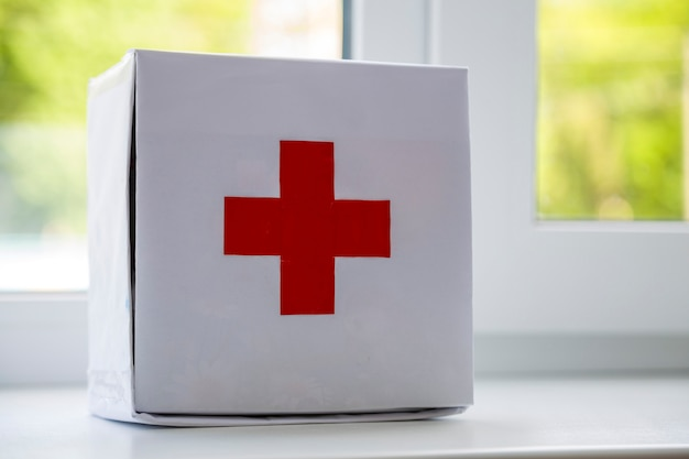 White first aid kit with red cross indoors on windowsill on blurred background