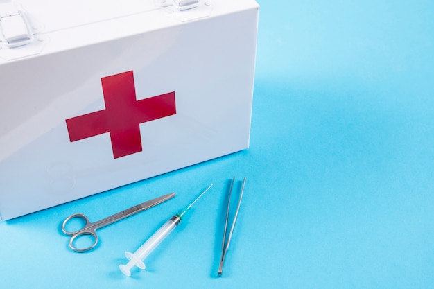 White first aid kit with scissor; syringe and tweezers on blue background