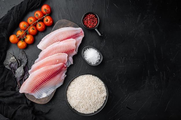 白身魚の切り身、バスマティライスとチェリートマトの材料、黒いテーブル、上面図