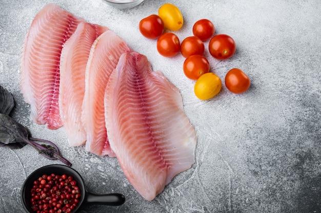 白身魚の切り身、バスマティライスとチェリートマトの材料、灰色の背景、上面図、テキストのコピースペース