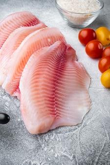 白身魚の切り身、バスマティライスとチェリートマトの材料、灰色の背景