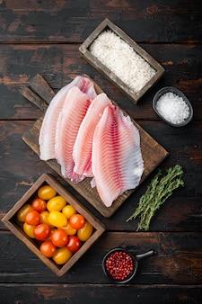 白身魚の切り身、バスマティライスとチェリートマトの材料、古い木製のテーブル、上面図