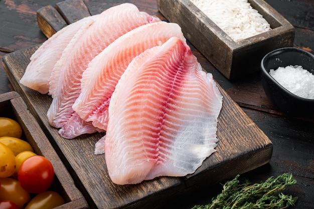古い木製のテーブルの上に、バスマティライスとチェリートマトの材料を使った白身魚の切り身
