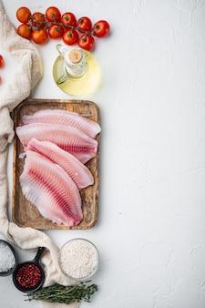 白身魚の切り身、バスマティライスとチェリートマトの材料、白い背景、テキストのコピースペースと上面図