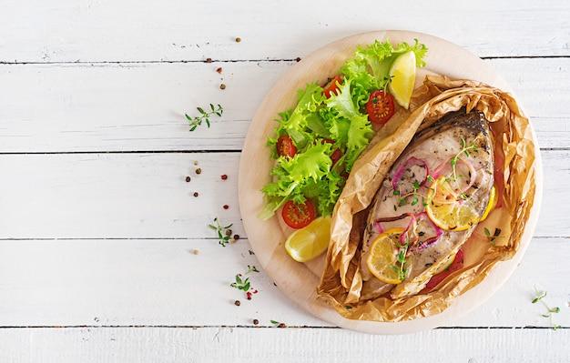 Стейк из белой рыбы (карп), запеченный в пергаментной бумаге с овощами. рыбное блюдо. вид сверху