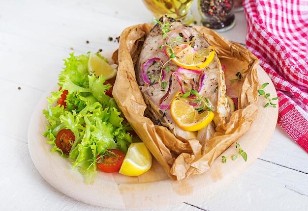 Стейк из белой рыбы (карп), запеченный в пергаментной бумаге с овощами. рыбное блюдо.