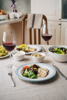 白身魚のステーキ、野菜サラダ、ソース、フムス、ブドウ、グラスワイン。キッチンで2人前