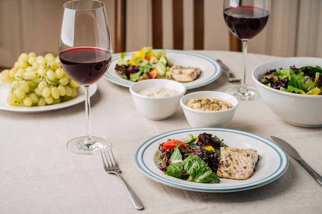 White fish steak with vegetable salad, sauce, hummus, grapes and glasses of wine. served for two in the kitchen