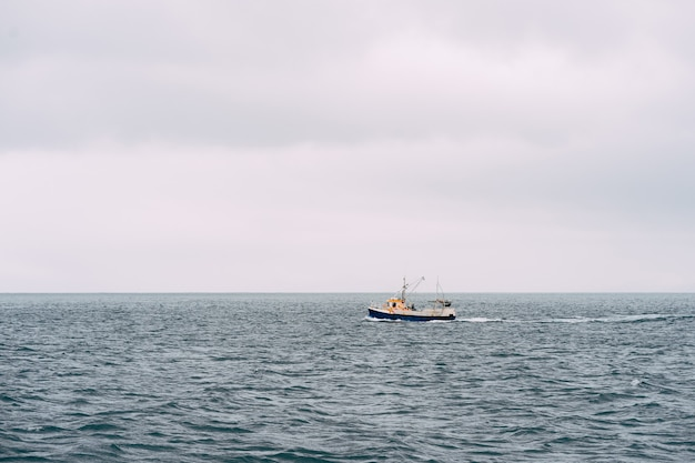 Белая рыбацкая лодка плывет в атлантическом океане недалеко от исландии