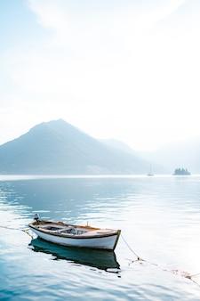 안개 속에서 산을 배경으로 침착 물에 흰색 낚시 보트.