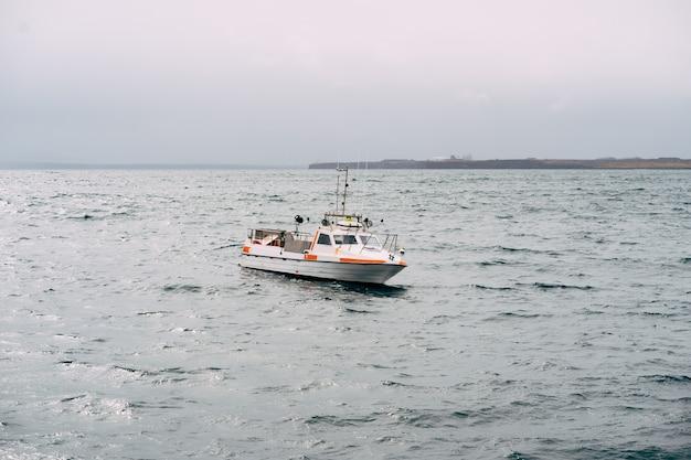 Белая рыбацкая моторная лодка плывет по атлантическому океану, вид сбоку на исландию