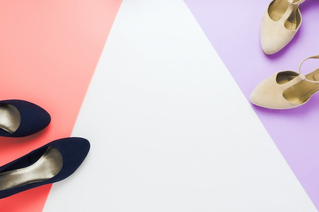 White flats and grey high heels shoes on violet, pink and white