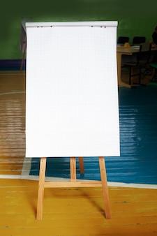 Белая лесть в клетке стоит на мольберте или деревянной подставке. это инструкция по записи текста или