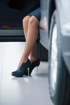 Pavimento bianco. foto ritagliata di una donna con i tacchi alti neri seduta in macchina
