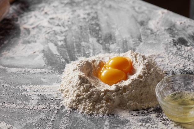 暗い台所のテーブルに白い小麦粉と卵黄