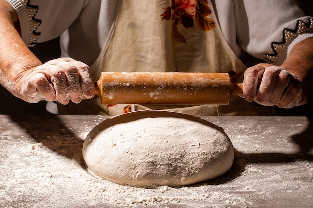 White flour flying into air as pastry chef in white suit slams ball dough on white powder covered table. concept of nature, italy, food, diet and bio
