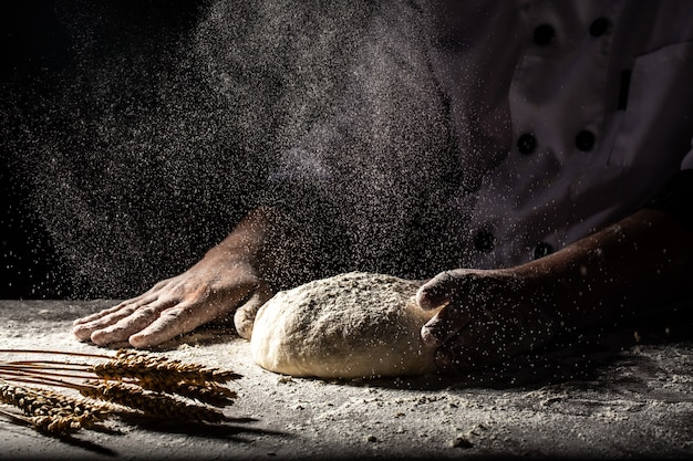White flour flying into air as pastry chef in white suit slams ball dough on white powder