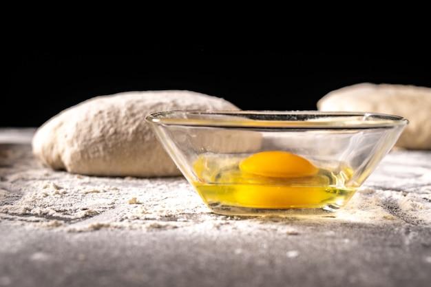 Белая мука с яйцами, маслом и тестом на кухонной доске, продукт