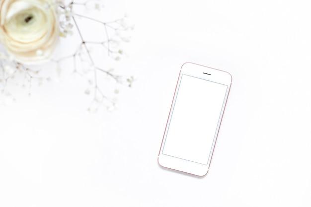 白い花と空白の画面と携帯電話