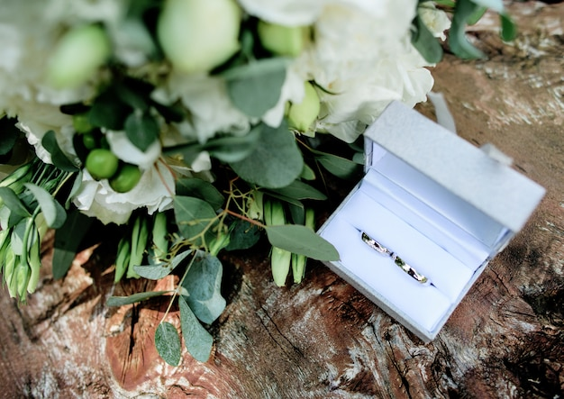 White flower bouquet next to little gift box with wedding rings