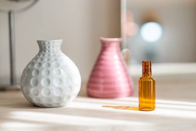 White flower ceramic vase, pink vase and reagent bottle on the table.