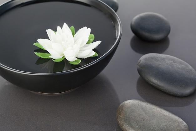 黒い小石に囲まれた黒い鉢に浮かぶ白い花