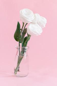 ライトピンクのガラス瓶の白い花のクローズアップ